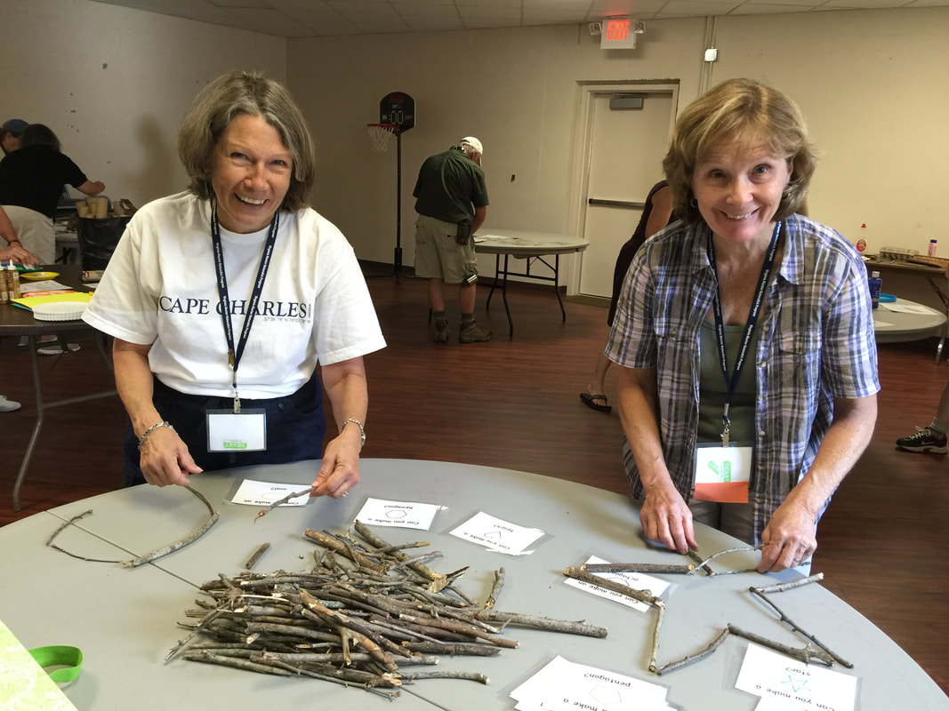 two people doing a craft with twigs on a table