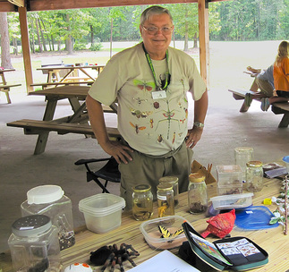 Clyde Marsteller standing with table covered in jars and cages with invertebrates.