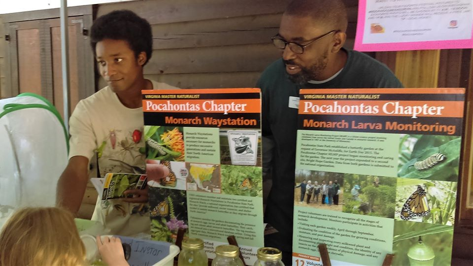 Two people at a display table with information about monarch butterflies, talking to a child looking through a magnifying glass