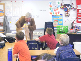 Clyde Marsteller taking creatures out of shopping bag in front of classroom of children.