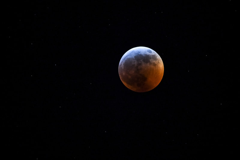 The moon, blue on top and blood red on the bottom in a black night sky dotted with stars