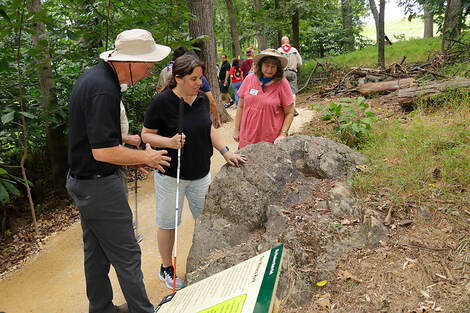 Woman holding white cane, touching a large boulder alongside a walking trail in a forest, while two volunteers speak to her about geology.