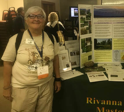 Woman with Virginia Master Naturalist nametag standing by Rivanna Master Naturalist display table