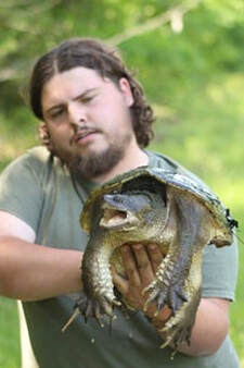 photo of man holding a snapping turtle