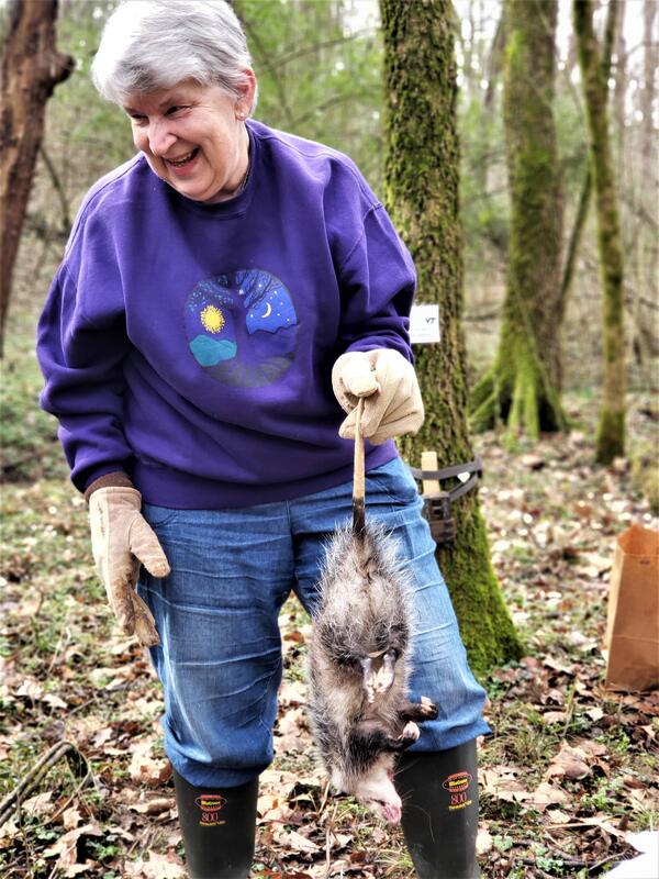 A smiling woman in a forest, wearing boots and gloves, holding a dead opossum by the tail