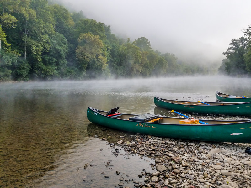 Three green canoes landed on rocky river shoreline with mist rising over the river and green forested hill in background
