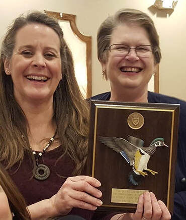 Two women holding an award plaque from Ducks Unlimited.